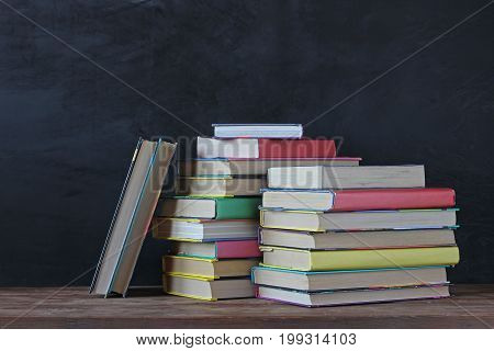 A stack of books on the background of a school blackboard. Back to school. Textbooks in the colored cover on the table.