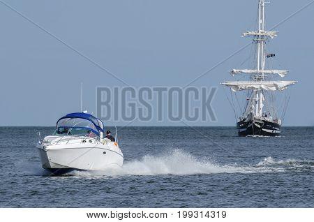 BALTIC SEA / POLNAND - 2017: Holiday entertainment. Motorboat and sailing ship at sea