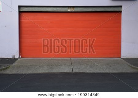 red garage door with grey concrete driveway