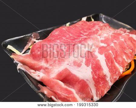 Fetta di maiale crudo nella piastra rotonda bianca sul tavolo di legno.