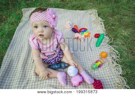 Portrait Of A Joyful Young Child Outdoors In The Park With Toys