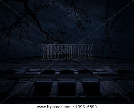 Horror scene of old grunge castle over dead tree moon and cloudy sky Spooky background Halloween concept