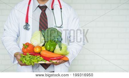A health professional or doctor holding a tray of healthy fruit and vegetables to promote eating healthy to prevent disease