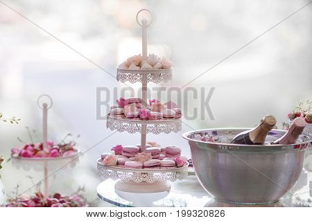 Stand with pink sweet macaroons and bottles on champagne on background.