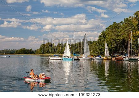 TRAKAI, LITHUANIA - 22 AUG 2015: Nice yahts reflecting in water of Galve lake, people enjoy summer day
