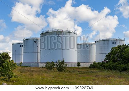 Silver oil tanks on the green grass field. Blue sky with clouds.