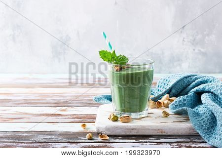 Glass of healthy green pistachio smoothie spirulina on old wooden background. Detox, diet, healthy, vegetarian food concept with copy space.