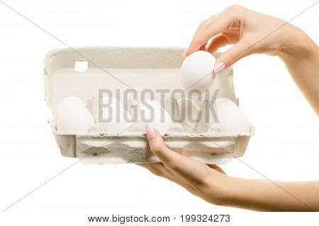 Eggs in a box in female hands on a white background isolation