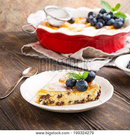 Piece of homemade cheesecake made from cottage cheese, decorated with blueberries and mint on wooden background. Healthy food concept with.