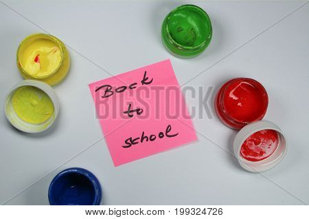 Sign ,,Back to school` on white background with paint colors/This is notice ,,Back to school` on white background with opened paint buckets colors.