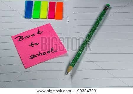 Sign ,,Back to school` on exercise book/This is notice ,,Back to school` on white exercise book with school aids.
