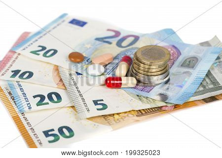 white and red tablets with euros banknotes and coins. Concept Pharmaceutical business cost of health medecine. Scattered pills. On white background