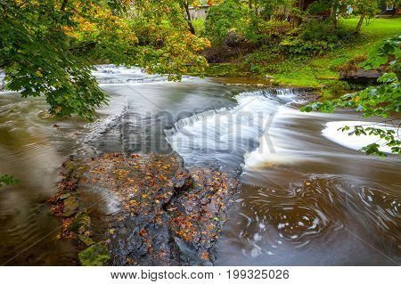 Joaveski waterfall on the river, with leaves, in Estonia