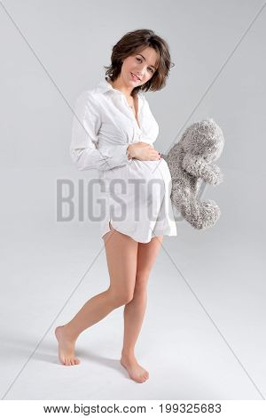 Pregnant woman holding soft toy. Pretty young woman carrying teddy bear