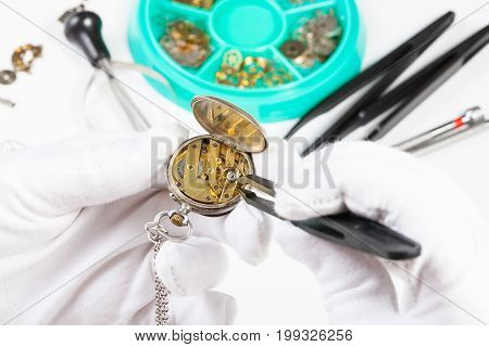 Adjusting Of Brass Pocket Watch By Tweezers