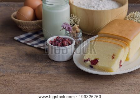 Slices of butter cake on white plate. Homemade butter cake with dried cranberries so delicious soft and moist. Tasty pound cake or butter cake served on wood table. Homemade bakery background concept.