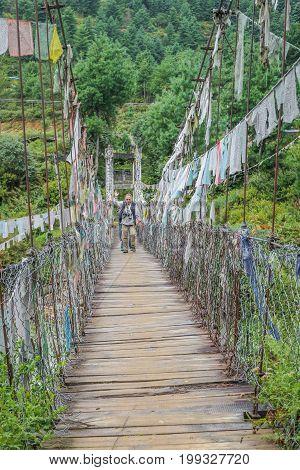 People walking on Bhutanese pedestrian suspension bridge with prayer flags in greenery area Bhutan Asia.