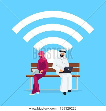 Wi-Fi concept. Young Muslim couple in a flat style of sitting on the bench. Arab men and women in traditional clothes read using a tablet pc. Vector illustration.