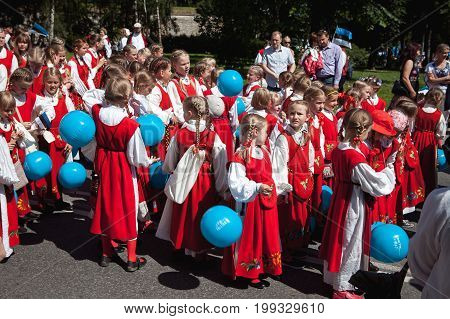 TALLINN, ESTONIA - 04 JUL 2014: Girls in national Estonian costumes with air balls preparing to ceremonial procession of Estonian song and dance festival
