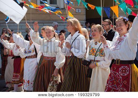 TALLINN, ESTONIA - 04 JUL 2014: People in Estonian costumes going at ceremonial procession of Estonian song and dance festival