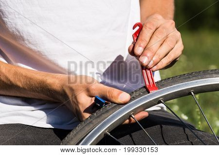 Repairing bicycle wheel outdoors during trip. Close up image of persons hands using tire levers to replace inner tube of bicycle wheel