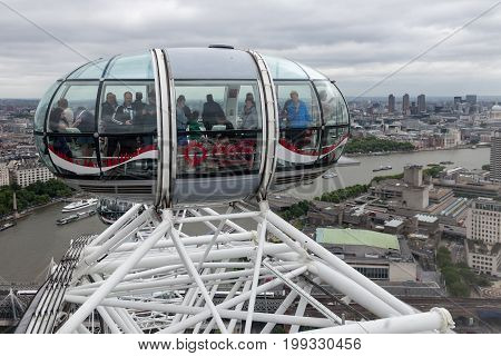 LONDON ENGLAND - JUNE 08 2017: Tourists in cabin London Eye with aerial view at London England