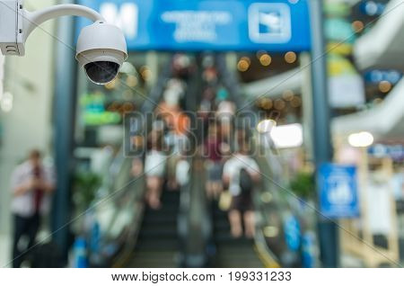 Security camera monitoring the store and escalator blur with bokeh background