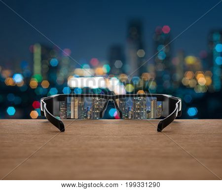 Cityscape focused in glasses lenses on the wooden over the abstract photo blurred of cityscape background business success concept