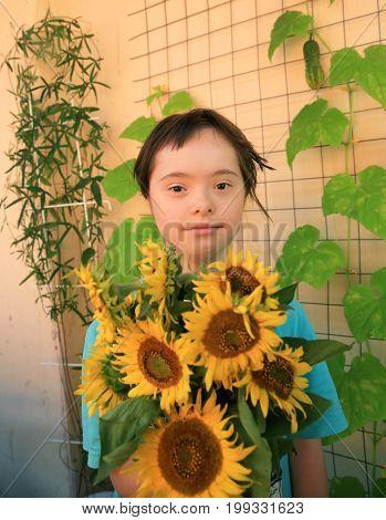 Little girl posing with sun flowers .