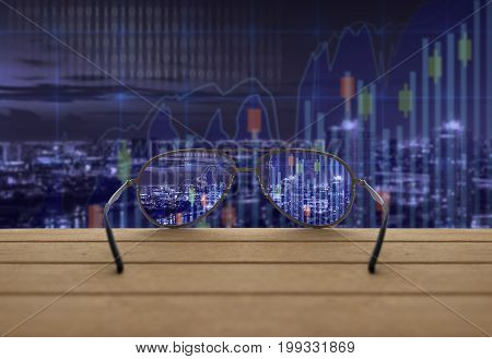 Stock exchange market trading graph focused in glasses lenses on the wooden over the abstract photo blurred of trading graph background business technology trading concept, 3D illustration