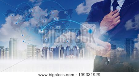 Double exposure of businessman using the tablet for sending the email on world map with network line over the cityscape background business conceptElements of this image furnished by NASA