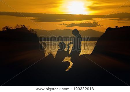 Silhouette of happy lover holding each other on the mountain over the sea and twilight sky valentine lover concept