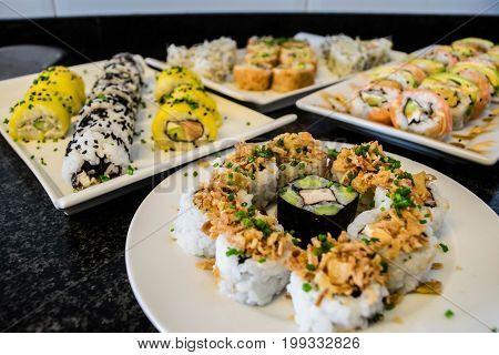 Sushi platter with salmon, mango, avocado served on white plate