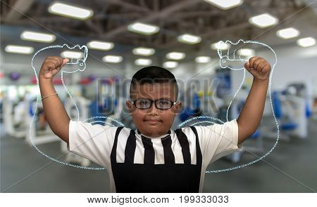 Asian strong children on Abstract blurred photo of fitness gym background.