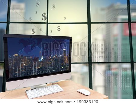 the computer on the wood table in front of the glass window over the blurred photo of cityscape background,