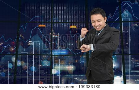 Asian Businessman looking at watch on theTrading graph over the cityscape at night and world map backgroundBusiness financial concept