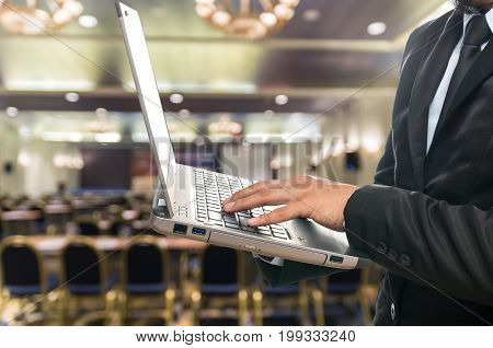 Businessman using the laptop on the Abstract blurred photo of conference hall or seminar room background