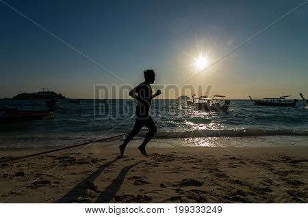 silhouette of running at sunrise time over the sea beach with lens flare