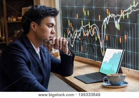 Asian Businessman sitting and using computer laptop showing trading graph beside the windows glass over the stock exchange trading graph screen background Business financial and forex concept