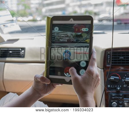 Bangkok Thailand - Aug 7 2016 : Hand holding Apple ipad mini2 tablet showing the Pokemon Go application at screen in the car over on the way photo blurred background on August 7 2016 thailand
