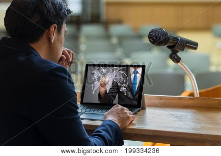 Businessman sitting and using computer laptop showing the connectionon dark blue color over Microphone on the speech podium over the Abstract blurred photo of conference hall Business meeting concept