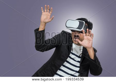 Asian Man wearing virtual reality in scared action on blue background include clipping path