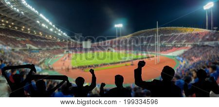The silhouette of fan club over the panorama of Abstract blurred photo of fan sport at stadium sport background concept