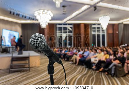 Microphone over the Abstract blurred photo of conference hall or seminar room with attendee background Business meeting concept