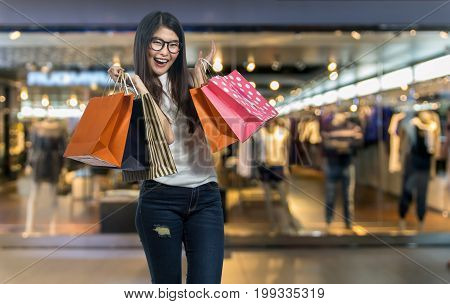 Happy young asian woman shopping in happy feeling and holding the product paper bag over the Abstract blurred photo of clothing store in a shopping mall shopping concept
