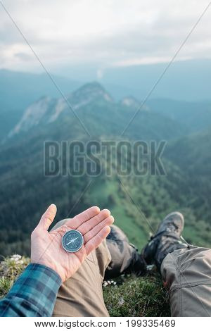Hiker young man with compass sitting in summer mountains and searching direction point of view.