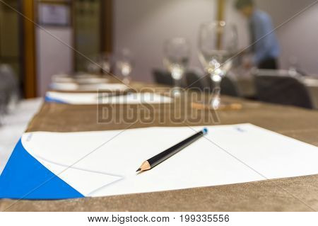 Pencil over the paper on the table of workplace with Glass of waterin the seminar or conference hall room Business meeting concept