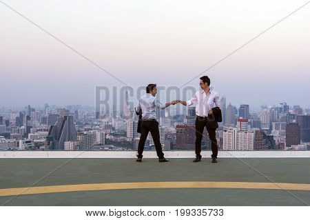 Fist Bumping Corporate Colleagues Teamwork between professional Couple businessman over the cityscape background at evening time Business success concept