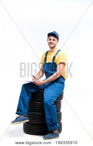 Tyre service worker sitting on a pile of tires