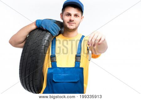 Worker in uniform holds tire and car keys in hands